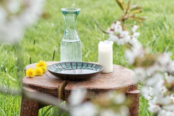 Schale, Wasserkrug, Kerze und Blüten auf einem Gartentisch - Copyright: Lars Timm