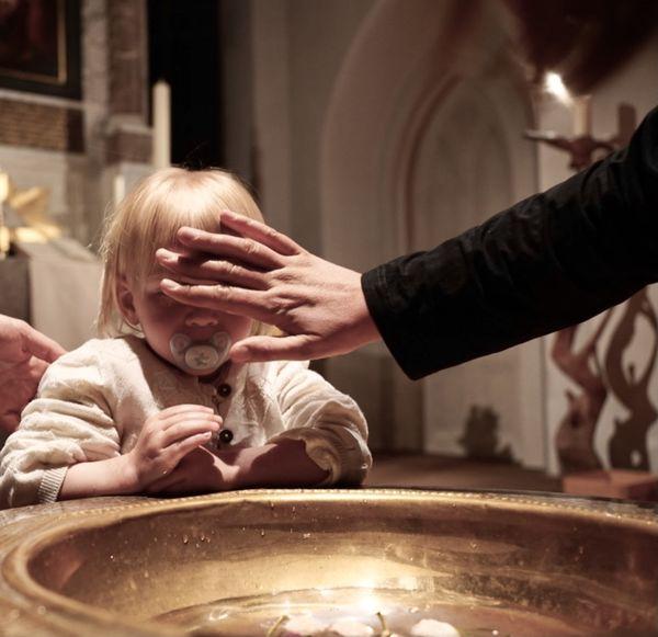 Kind, das am Taufbecken gesegnet wird  - Copyright: Marc Timm
