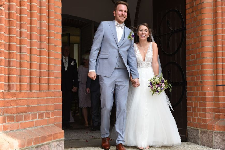 Hochzeitspaar geht durch Kirchentür - Copyright: Heß Fotografie, Katrin Heß