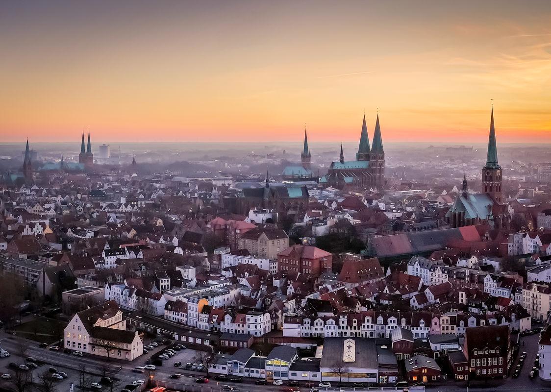 Eine Stadtansicht Lübecks im Sonnenaufgang mit den 7 Türmen der 5 Altstadtkirchen - Copyright: Oliver Beck