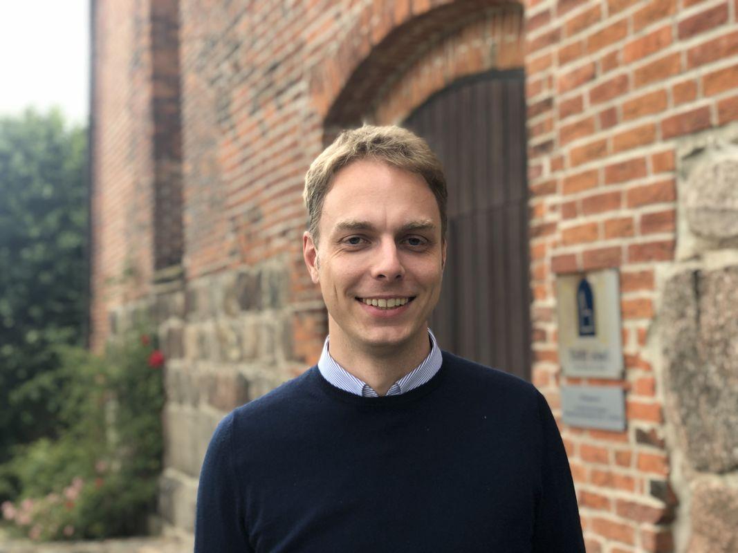 Ein Mann Anfang 30, Oliver Erckens, vor einer Kirchenwand - Copyright: Oliver Erckens privat