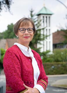 Pastorin Ulrike Lenz. Eine Frau Mitte Fünfzig mit roter Strickjacke. Im Hintergrund ist die Kirche von Wentorf zu sehen. - Copyright: Elisabeth von Schönberg