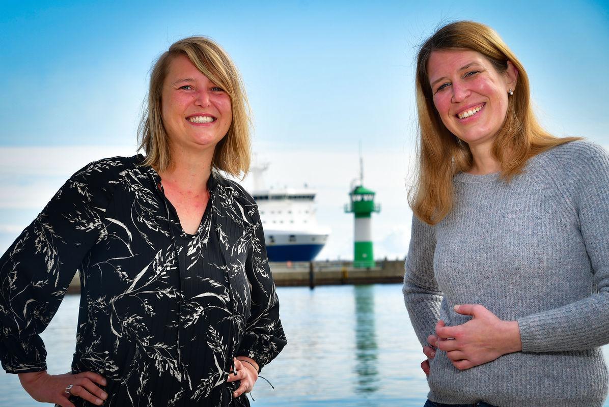 Die Pastorinnen Sarah Stützinger und Inga Meißner in Travemünde. Im Hintergrund ein Leuchtturm und ein Schiff